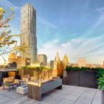 Exterior of rooftop appointed with metal planters and a seating area with fire pit, surround by other New York buildings.