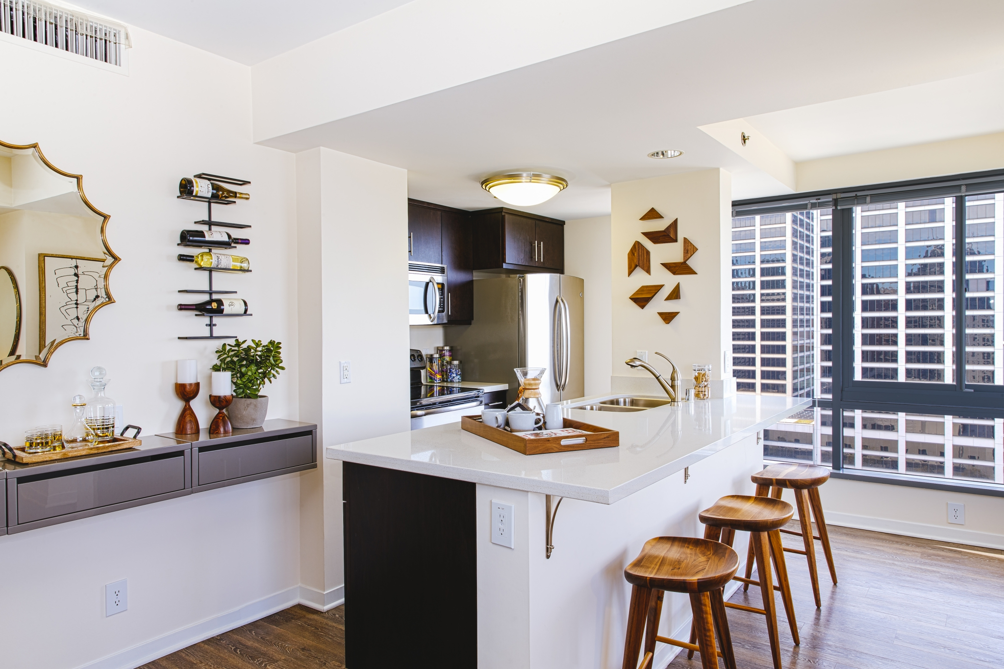 White kitchen with countertop bar, barstools and stainless steel appliances.
