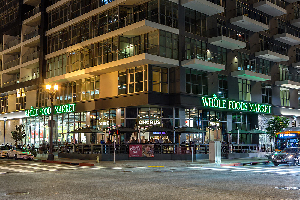 Street-level exterior of corner of apartment building showing Whole Foods Market on ground floor.