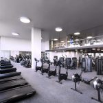 Interior of very large fitness center with multiple rows of exercise machines.