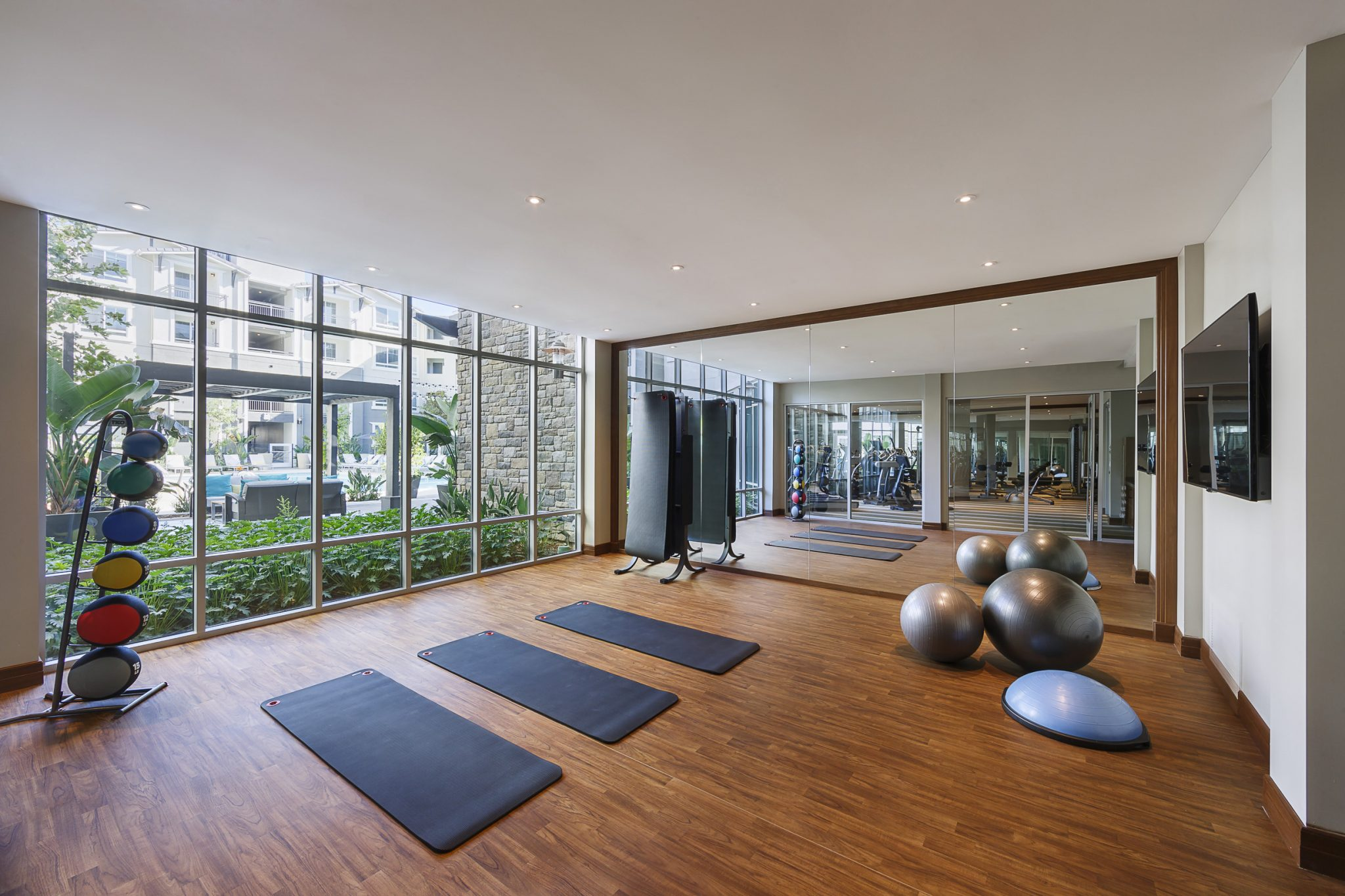 Interior of yoga studio with exercise balls, yoga mats and medicine balls in front of mirrored wall.