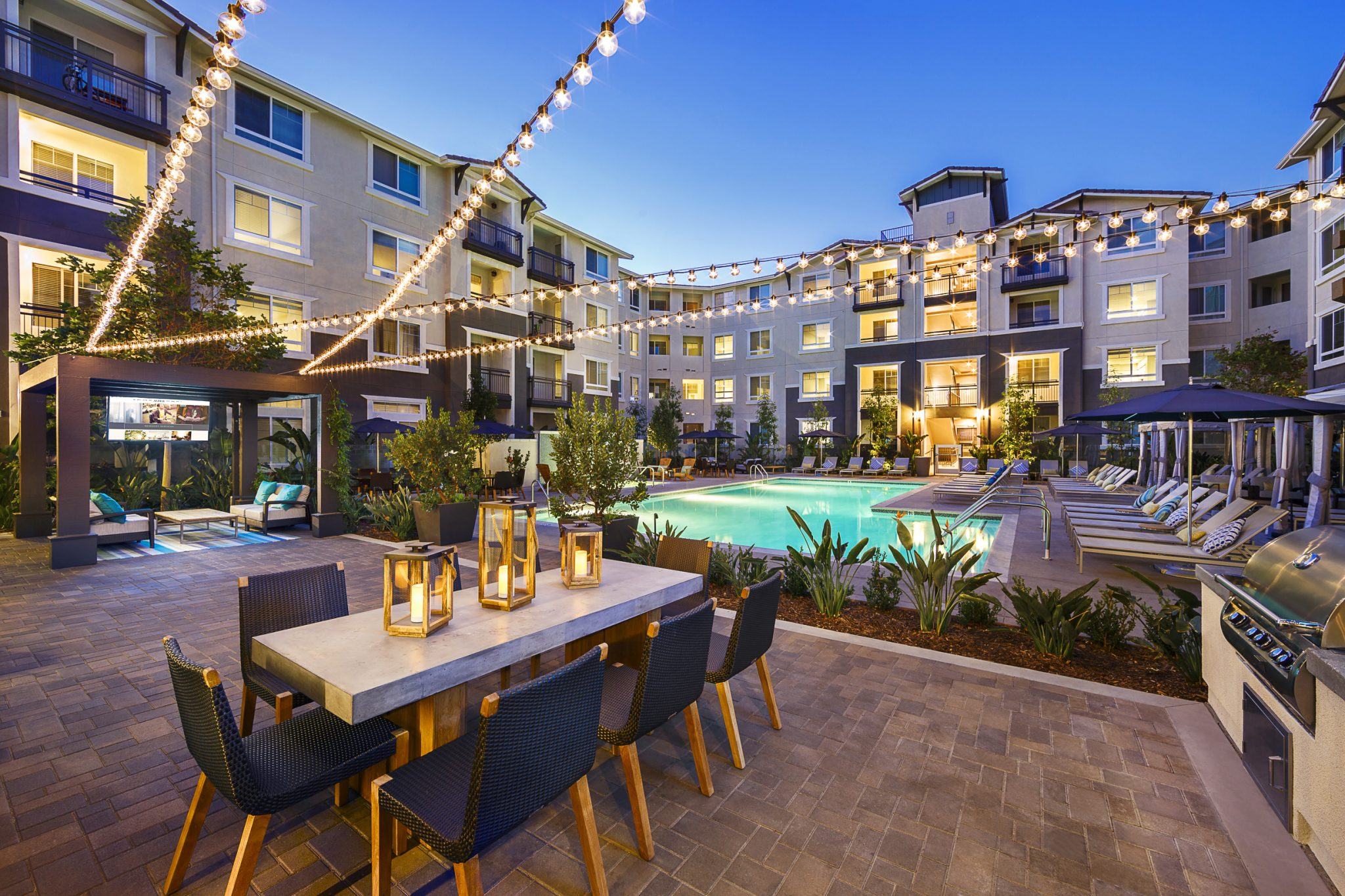 Exterior of apartment complex courtyard with barbeque, dining table and cafe lights overhead with pool in background