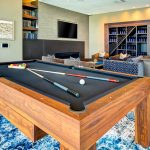 Interior of game room with pool table, fire place, large-screen television and couches
