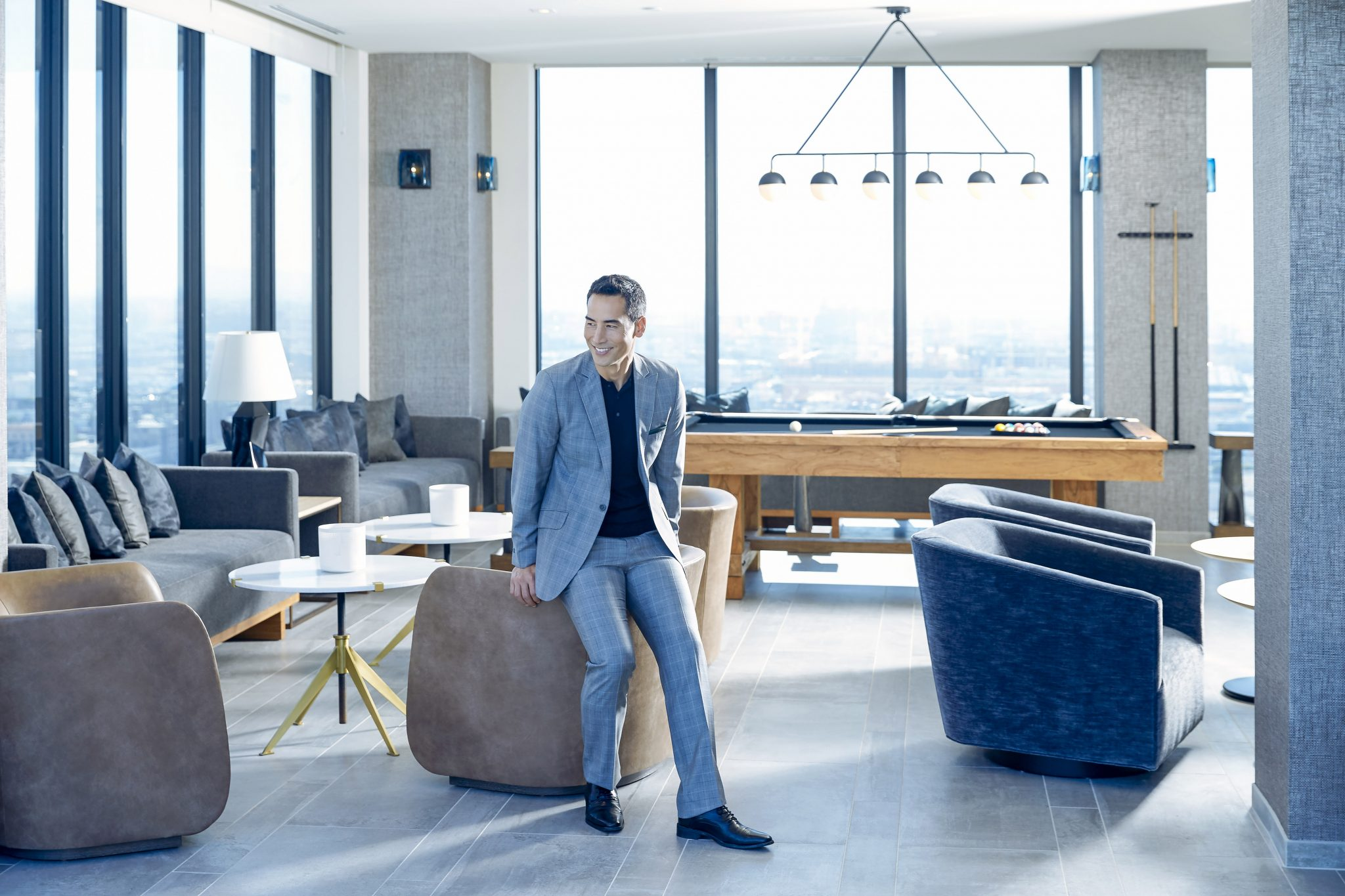 Interior with man in suit leaning on the back of a chair in a modern game room with pool table and city views ch