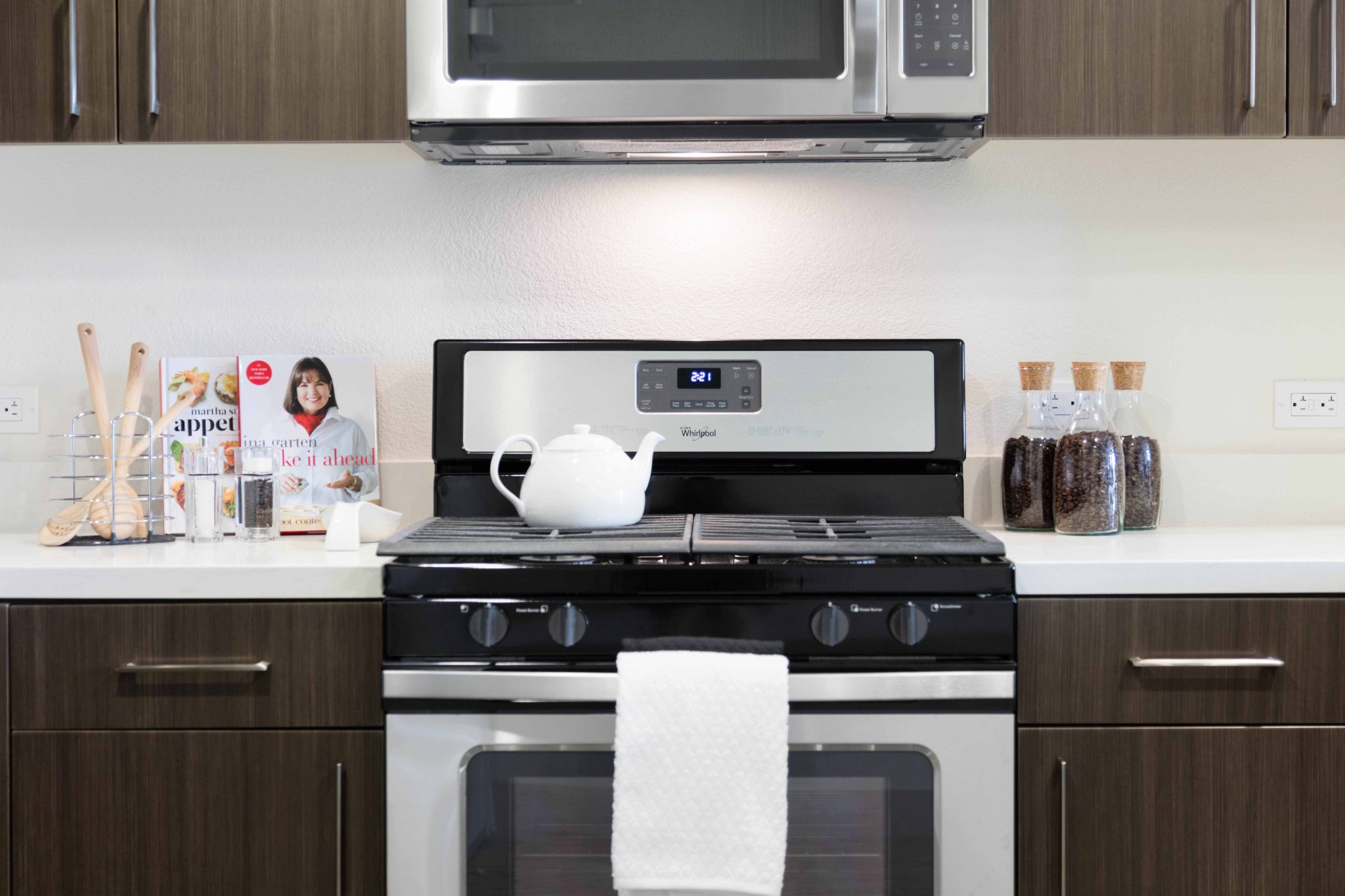 Stainless steel stove and cooktop in kitchen with dark cabinets
