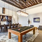 Interior of game room with pool table and bar height seating