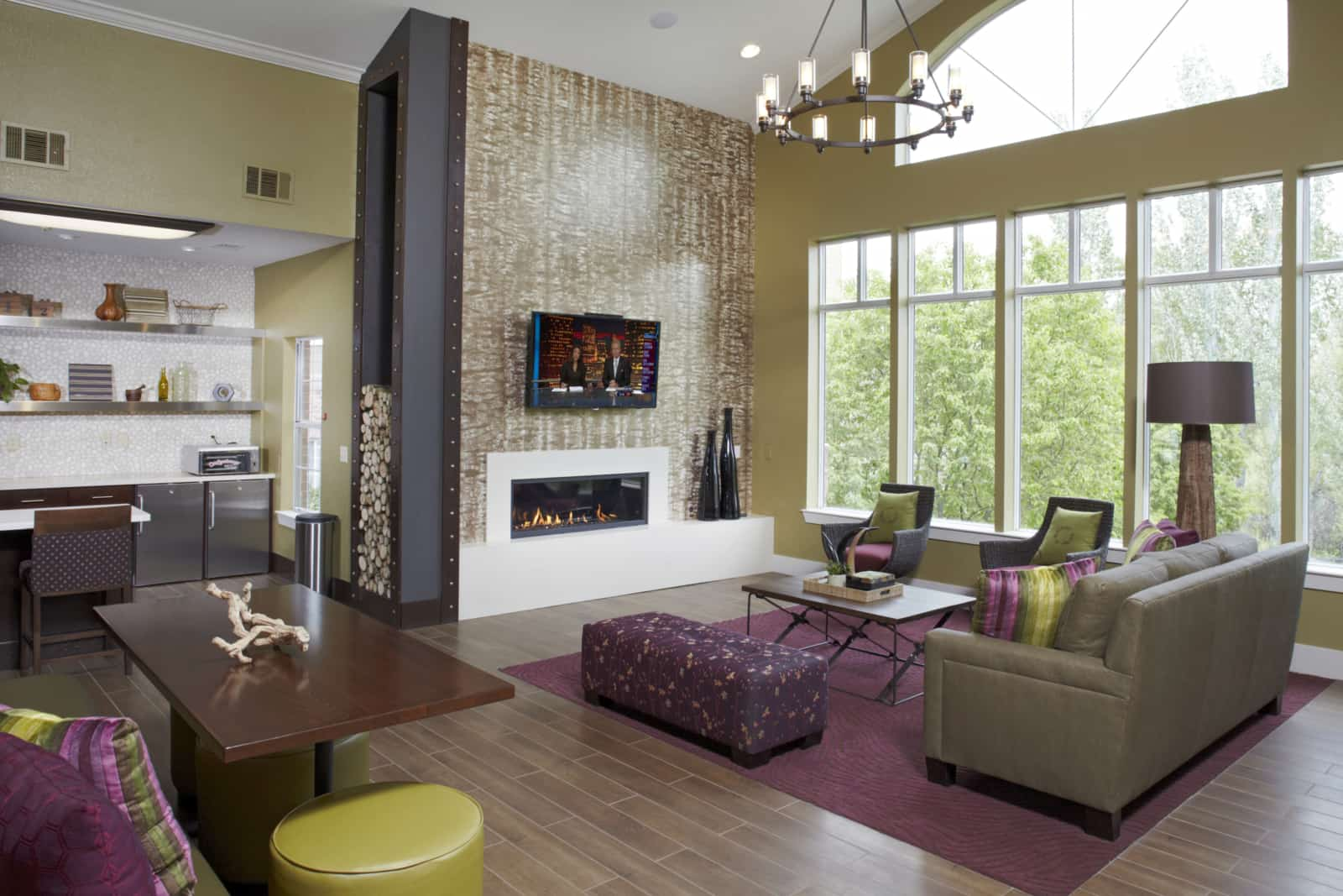 Interior of common area with couches, chairs, coffee table and a kitchen area off to the left.