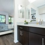 Open plan bedroom with bathroom vanity in foreground and bed in background.