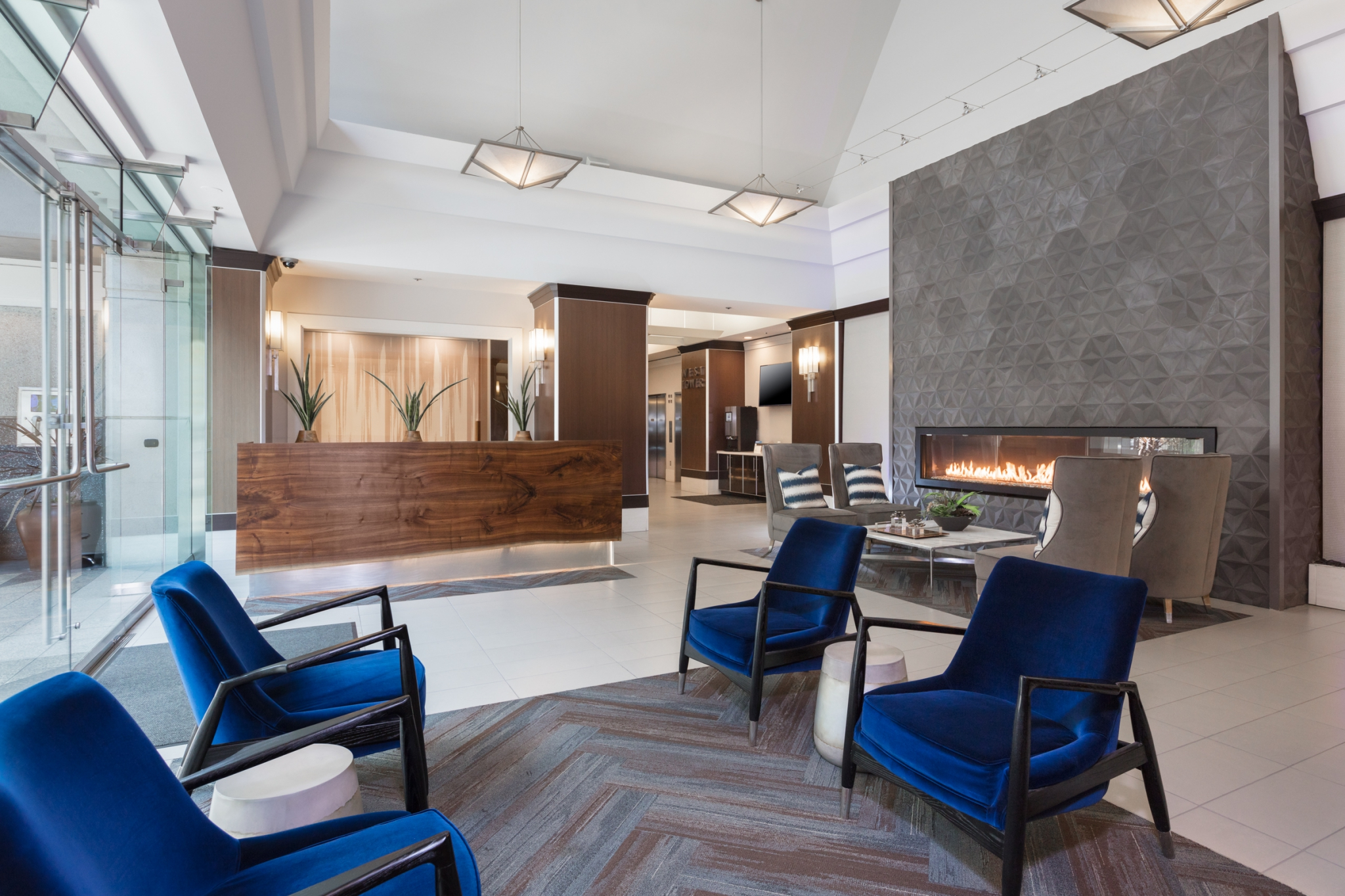 Lobby reception areas with chairs, coffee table and a long gas fireplace.