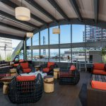 Covered outdoor area with chairs and tables with a view of the San Francisco Bay Bridge.