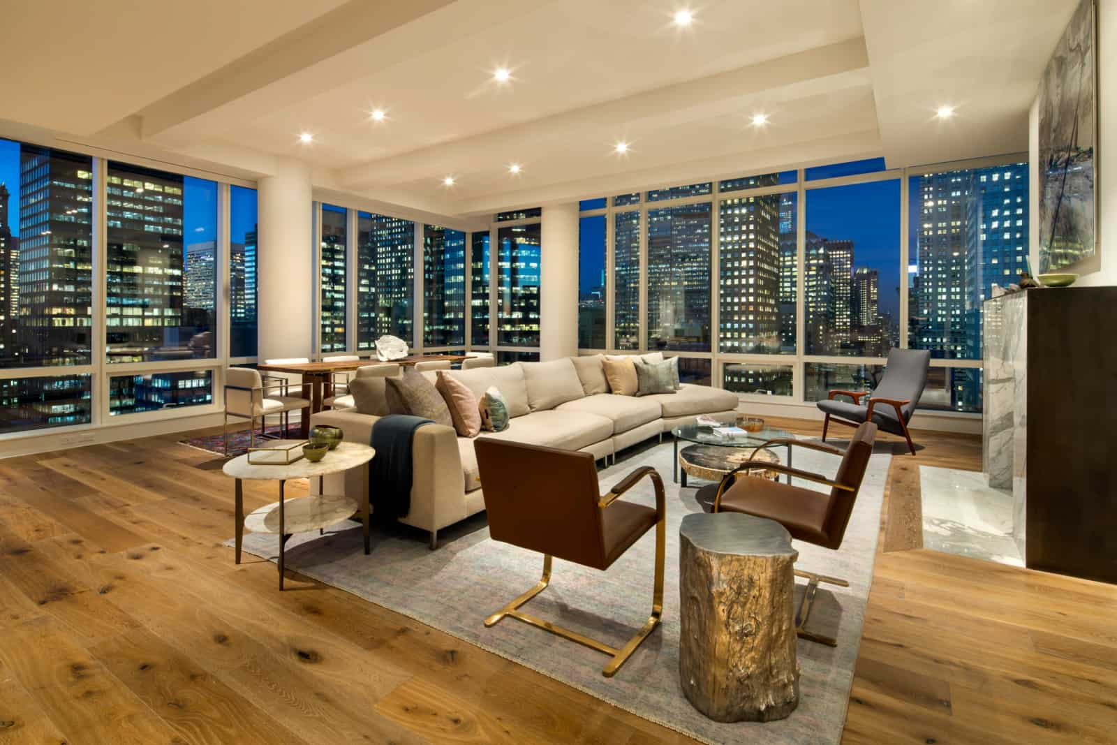 Large open plan apartment with living room area with fireplace, dining table, and windows on two sides with city views.