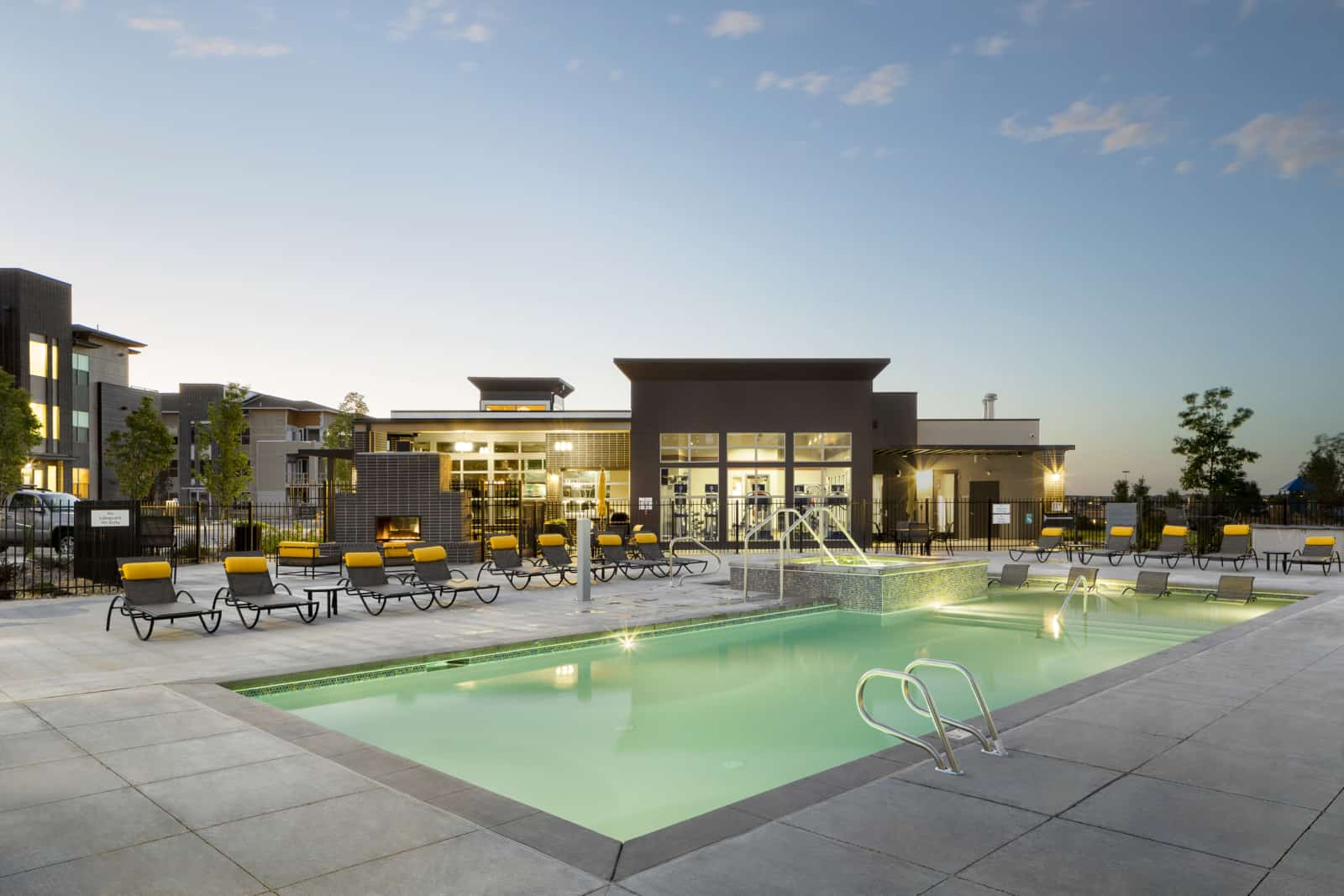 Exterior of pool with lounge chairs, outdoor fireplace and apartment building in background.