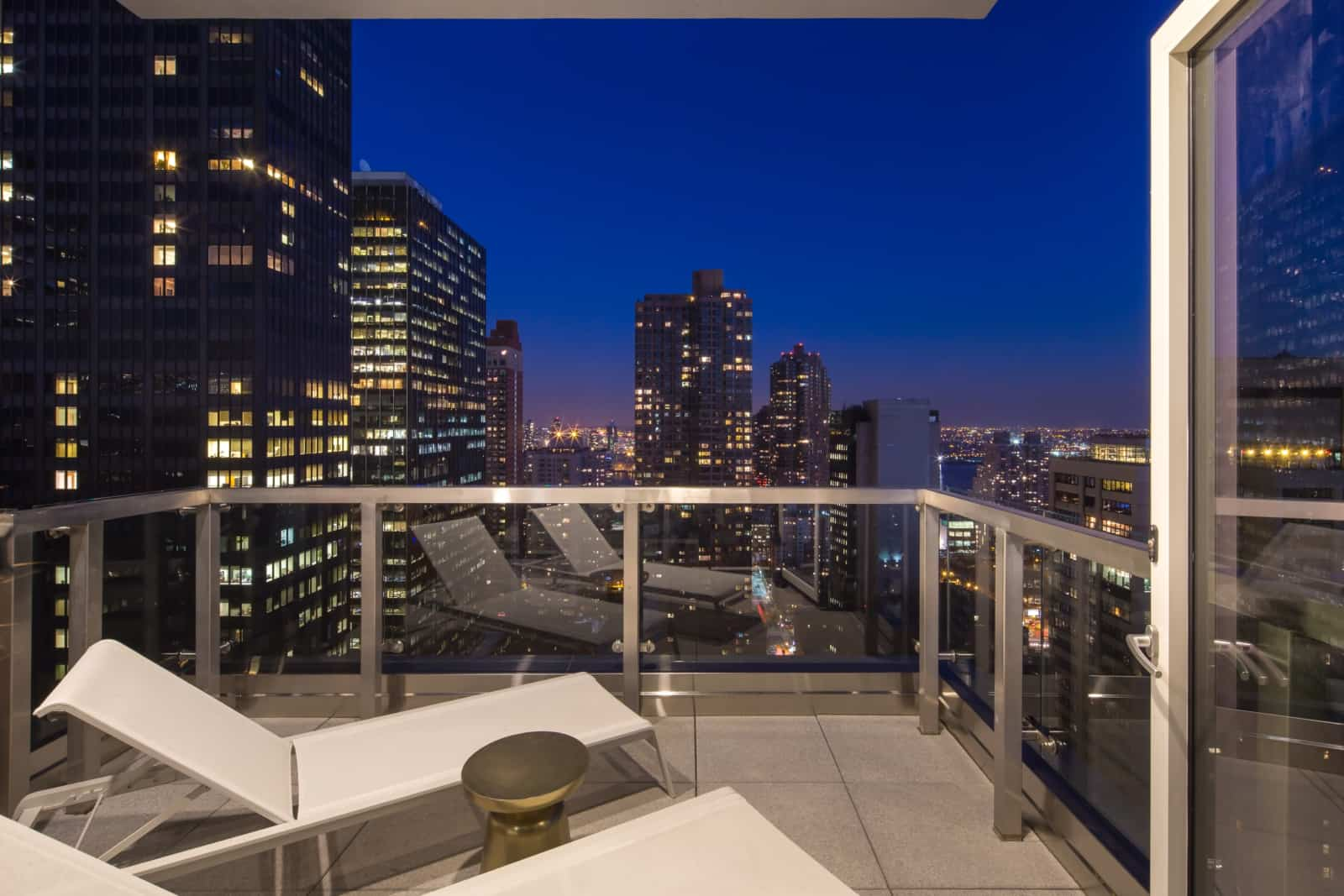 Apartment balcony with lounge chairs overlooking cityscape.