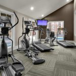 Fitness center with various cardio equipment and TV.