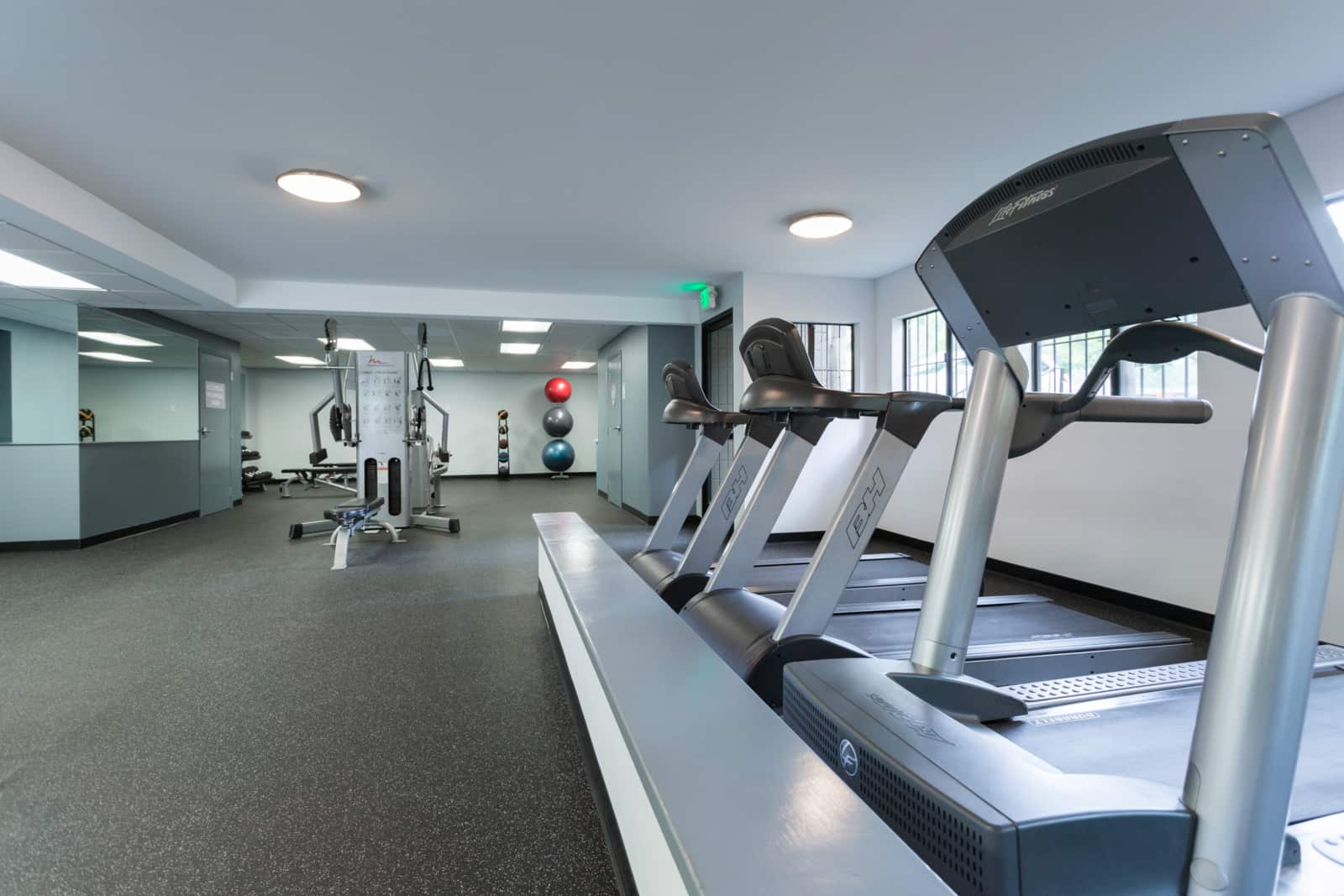 Interior of fitness center with treadmills, exercise balls and other exercise machines.
