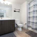 Apartment bathroom with shower, toilet and vanity.