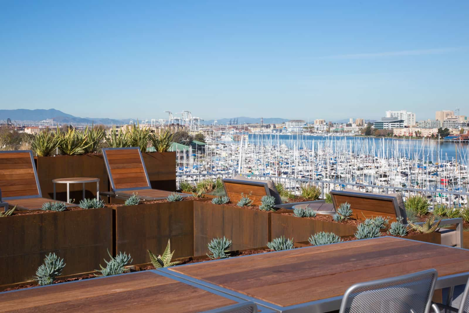 Rooftop lounges, table and chairs with marina view in background.