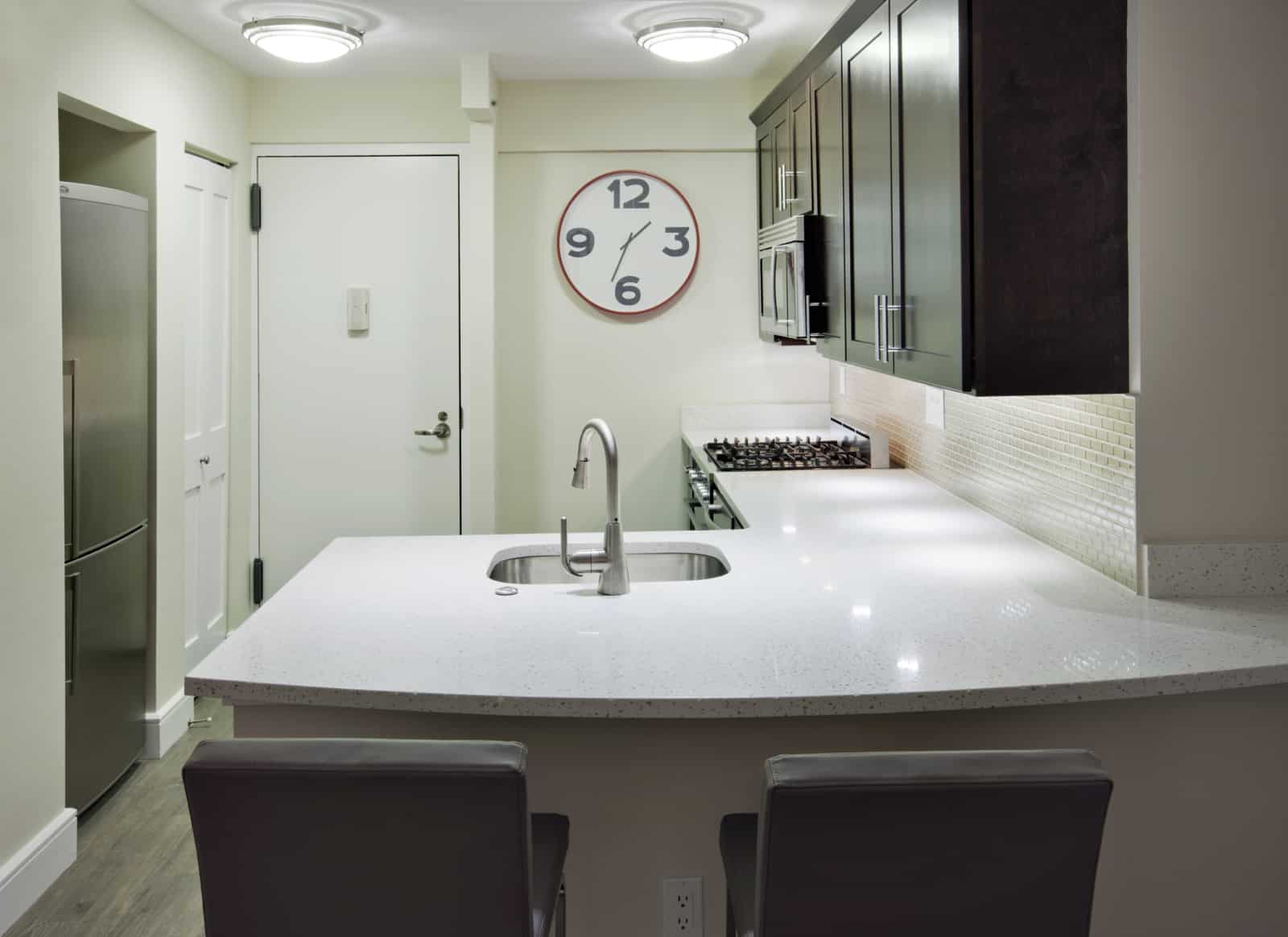 Interior of apartment kitchen with stainless steel appliances, white countertop, and seating.
