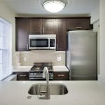 Interior of apartment kitchen with stainless steel appliances and white countertop.