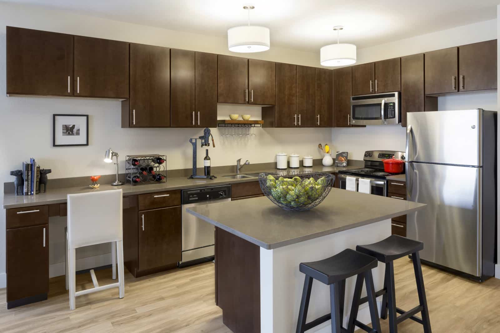 Interior of kitchen with stainless steel appliances, central island with seating.