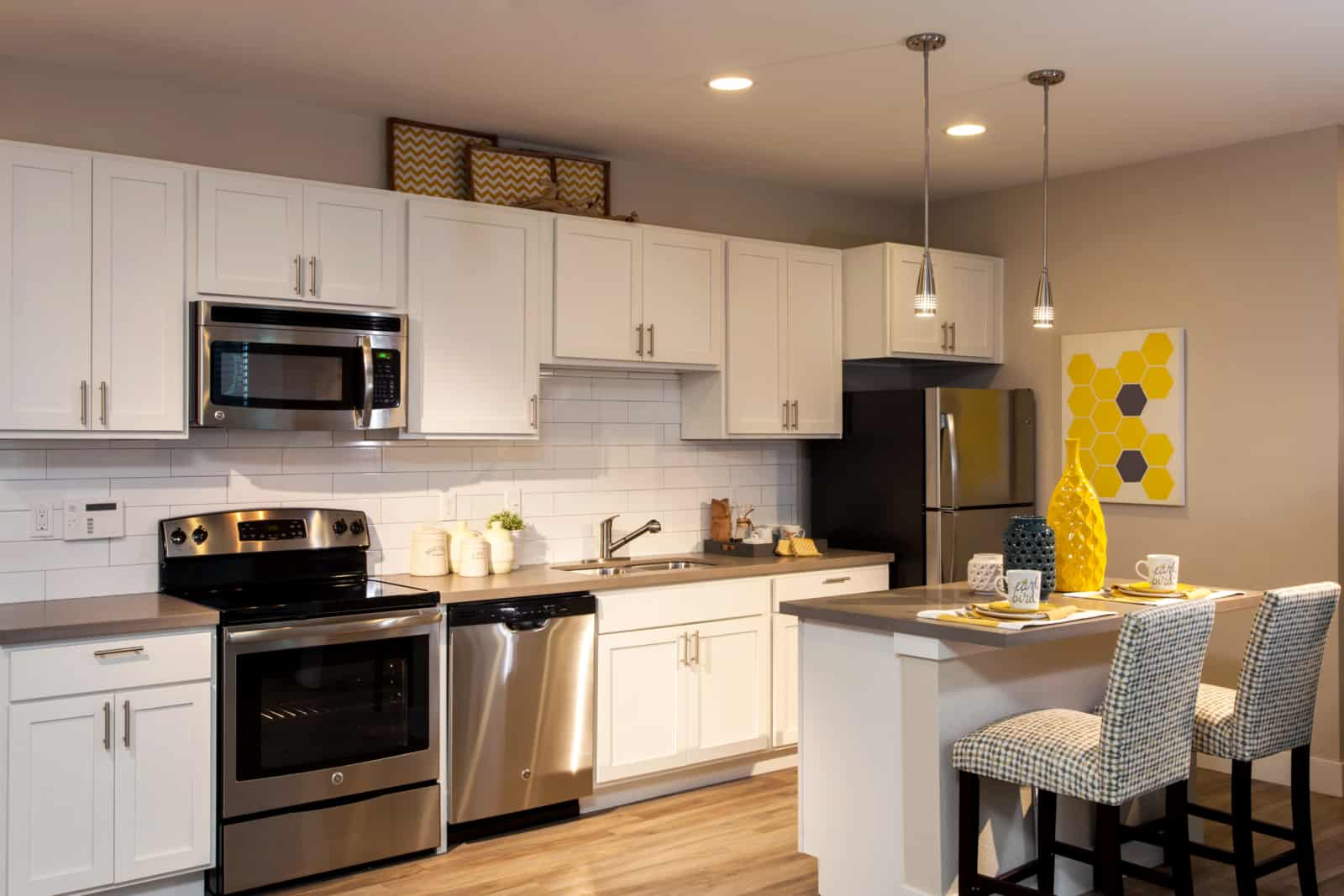 Open kitchen with island dining, stainless steel appliances and white cabinets.
