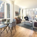 Modern apartment living room with windows on two side, dining table, and city views.
