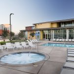 Hot tub, pool and lounge chairs with the apartment building in the background.