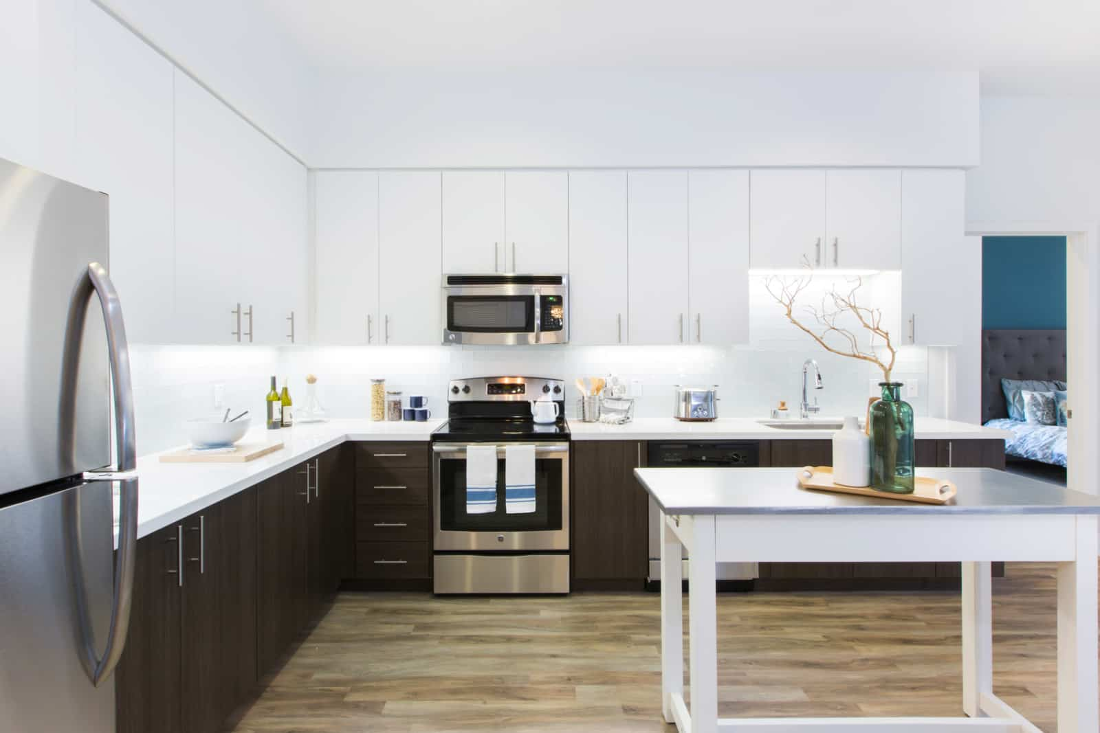 Modern kitchen with stainless steel appliances, white top cabinets and dark bottom cabinets and a view of a bedroom in peeking through a doorway.
