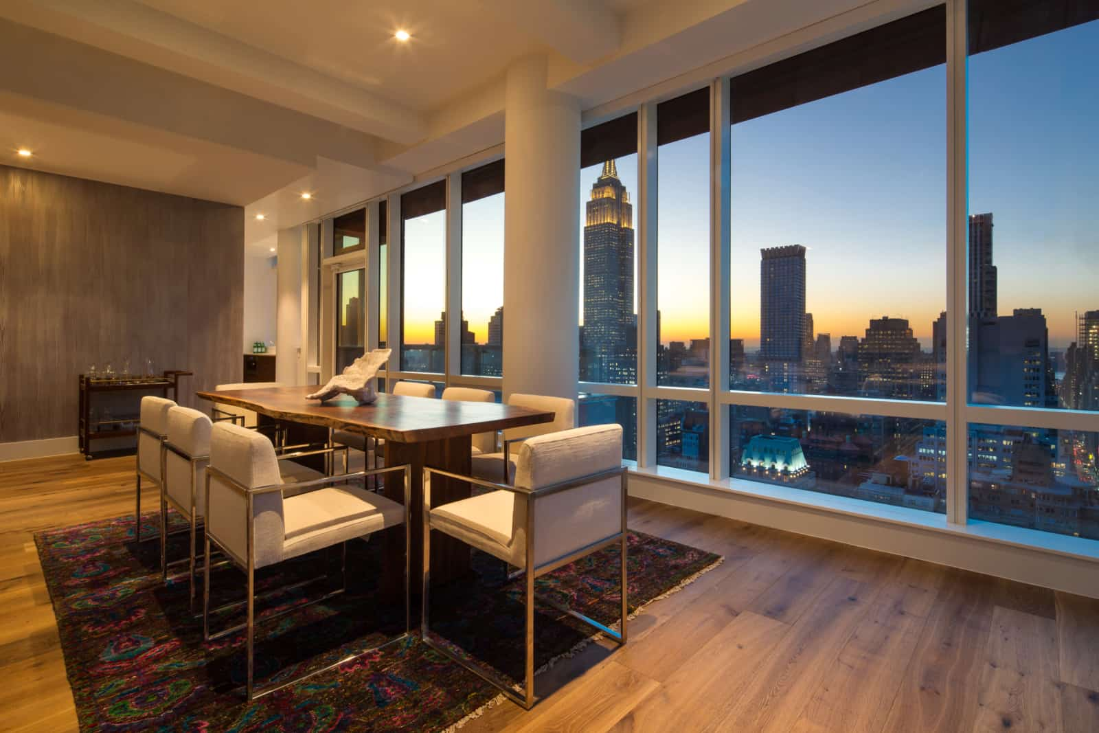 Modern apartment dining room with wall of windows and city views.
