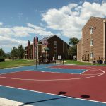 Basketball court with apartment building in the background.