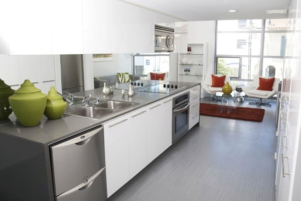 Interior of modern kitchen with stainless steel appliances and sitting area in the background.