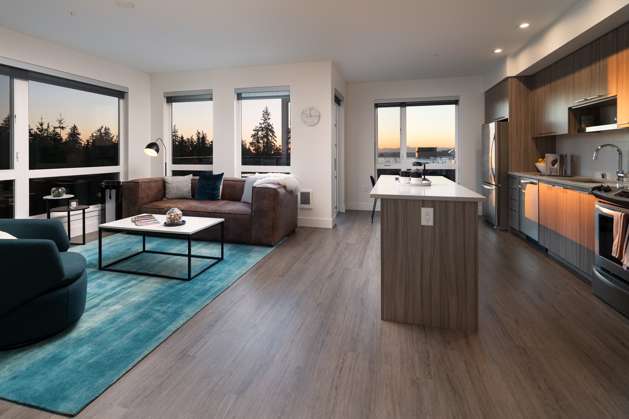 Interior of modern apartment with open kitchen, seating area with windows on two walls.