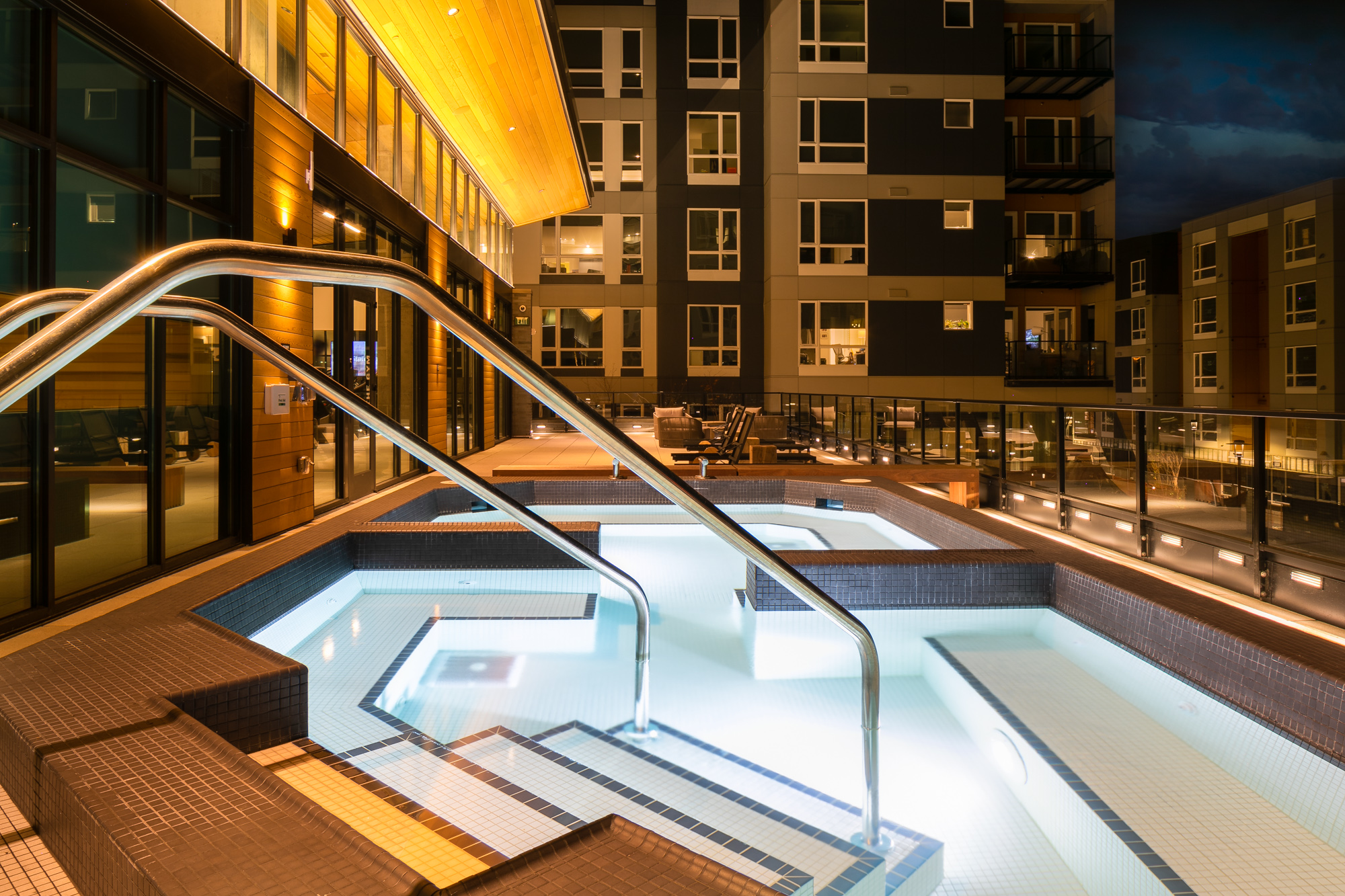 Exterior of large tiled spa pool with apartment complex in background