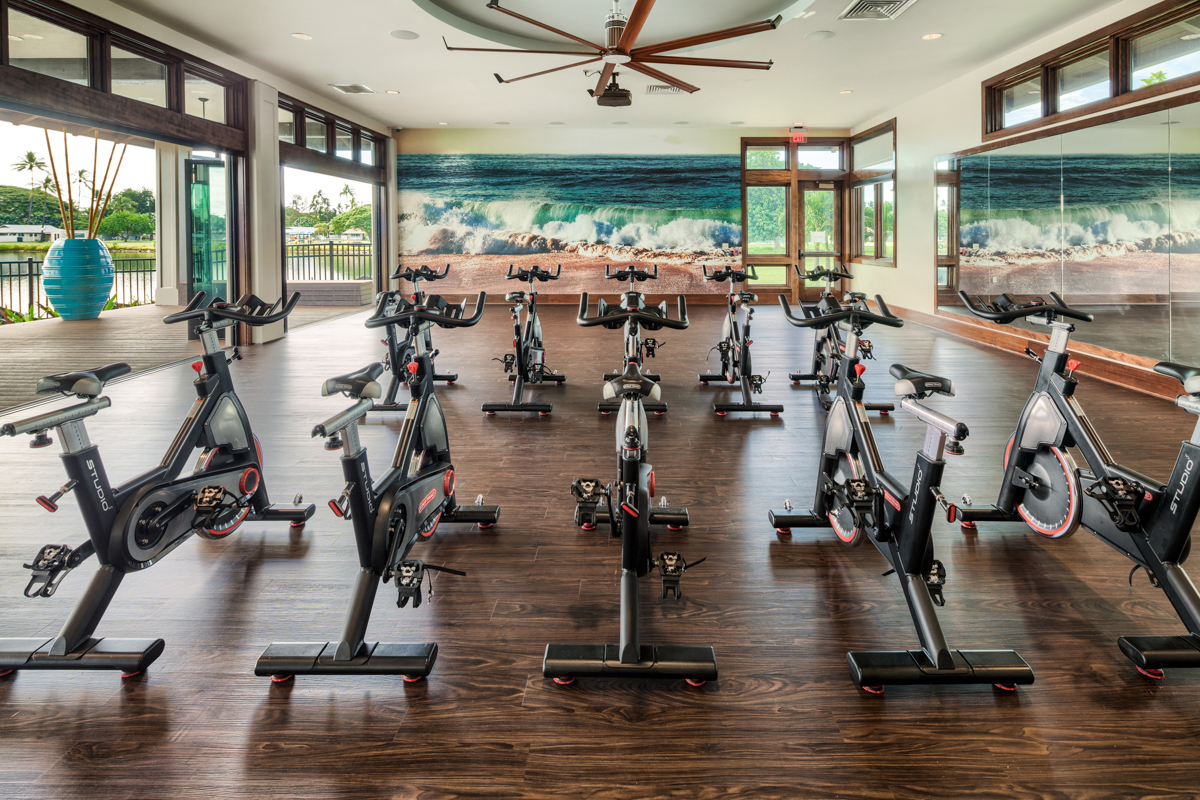 Interior of exercise studio with spinning bikes and walls open to the outside.