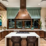 Interior of large kitchen with stainless steel appliances, central island with cooktop and seating.