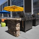 Close up of BBQ grills in the courtyard. with umbrellas in the background.