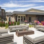 Exterior of glass-walled fire pit and couches with apartment buildings in the background