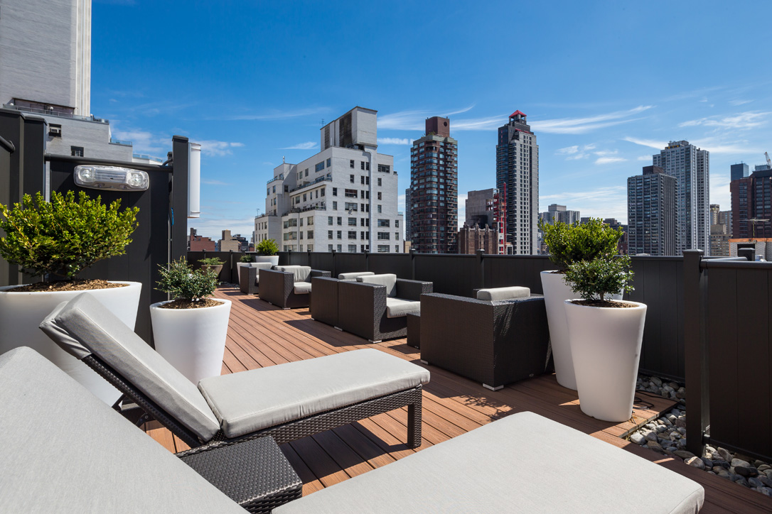Exterior of outdoor courtyard with lounge chairs, side tables and views of the city.
