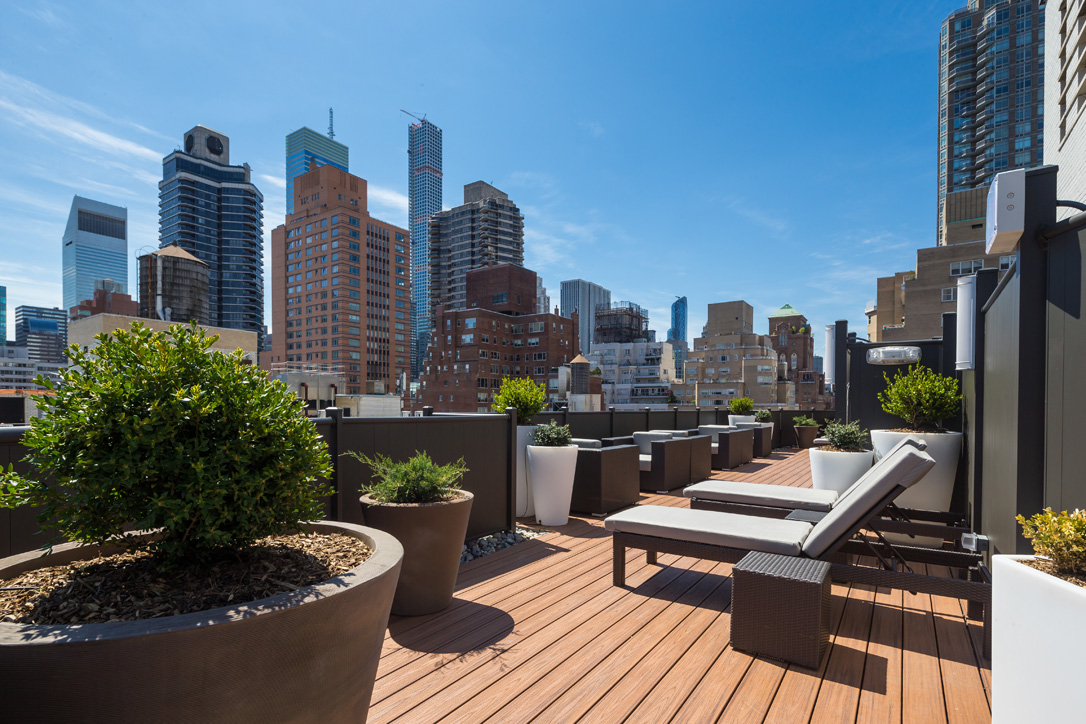 Exterior of roofdeck with lounge chairs, planters and a view of the city in the background.