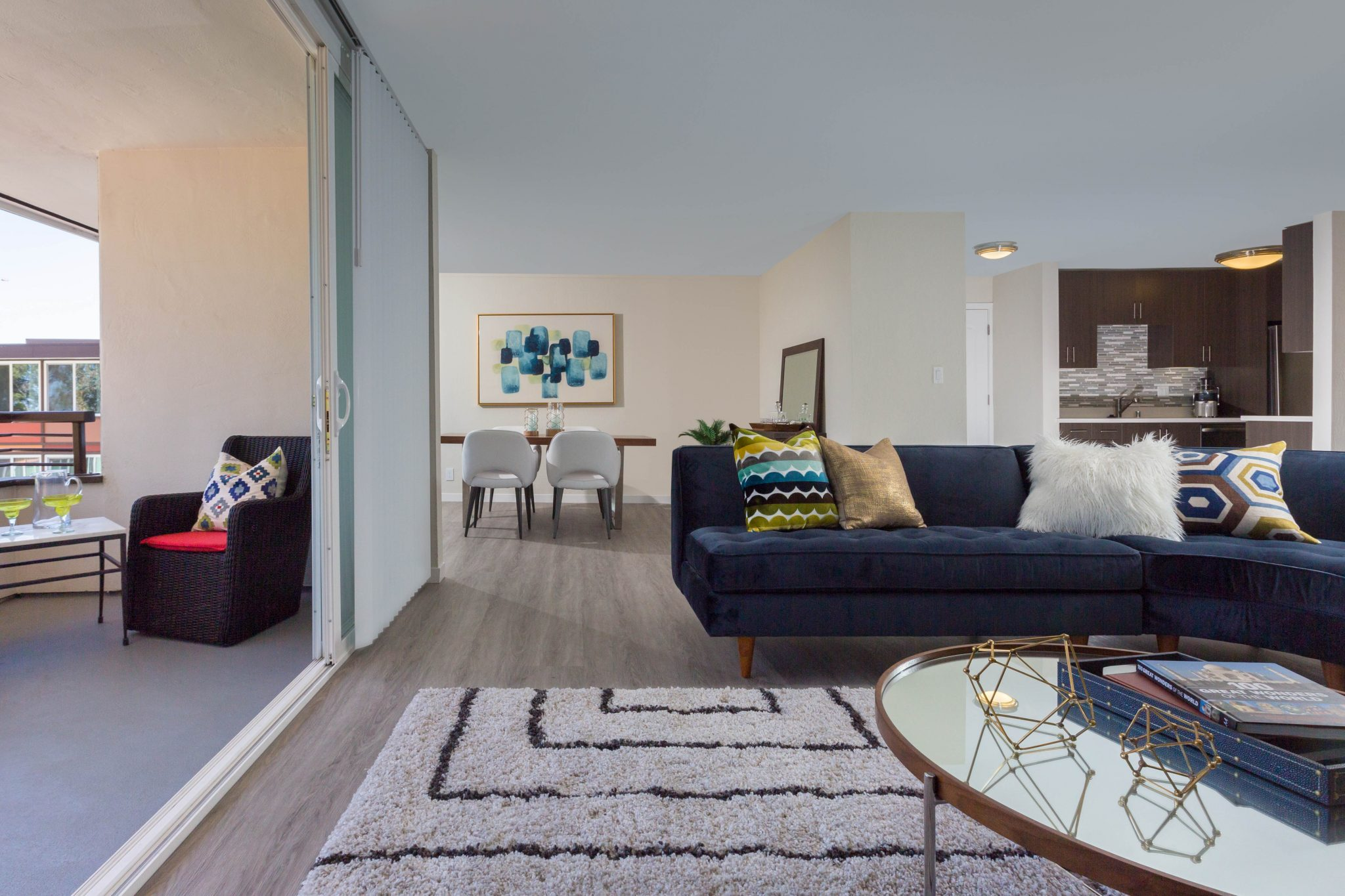 Open floor plan apartment interior of living room with dining area and kitchen in background and patio deck to the side.