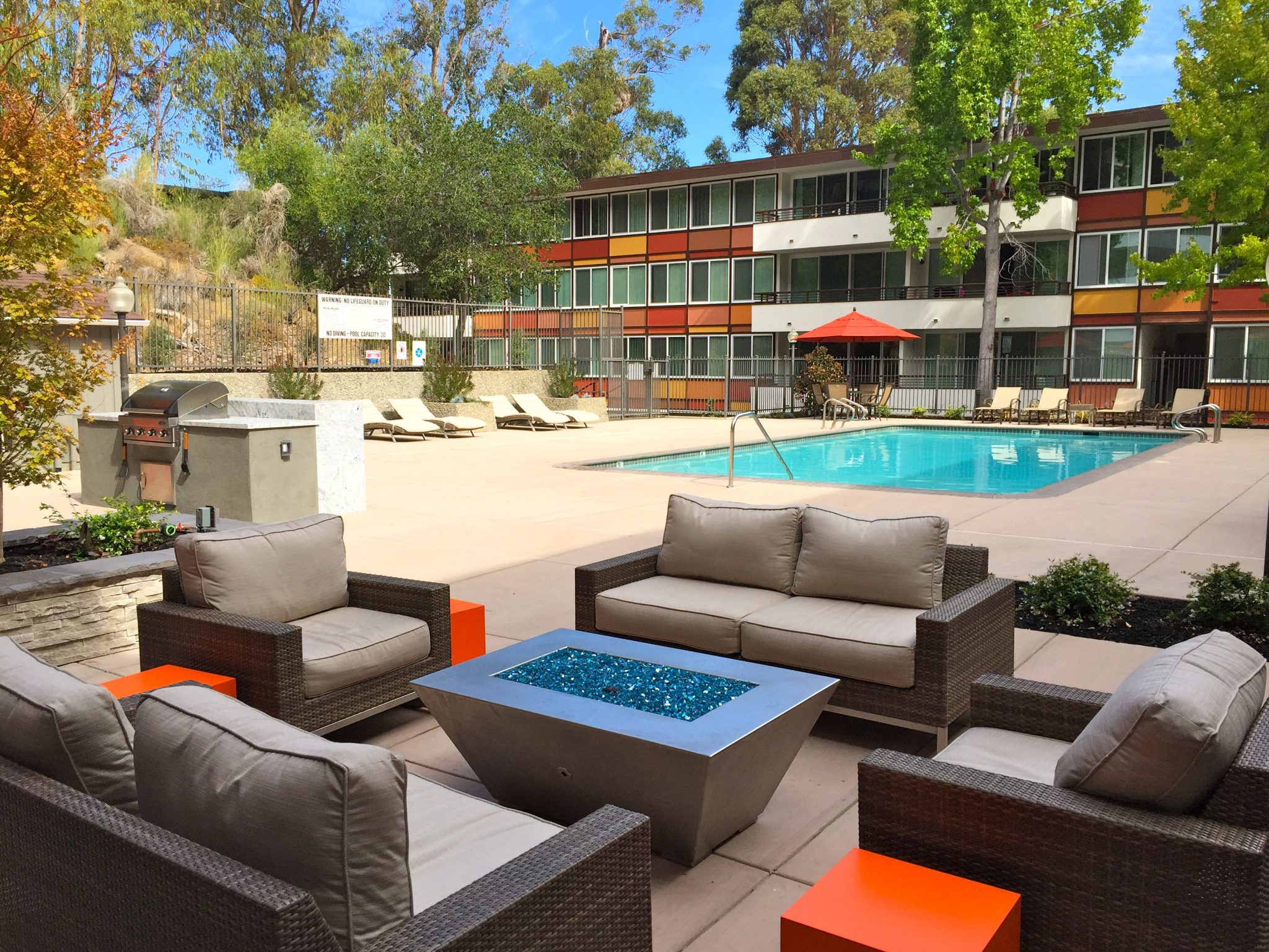 Exterior of pool deck with modern outdoor couches with fire pit in the foreground.