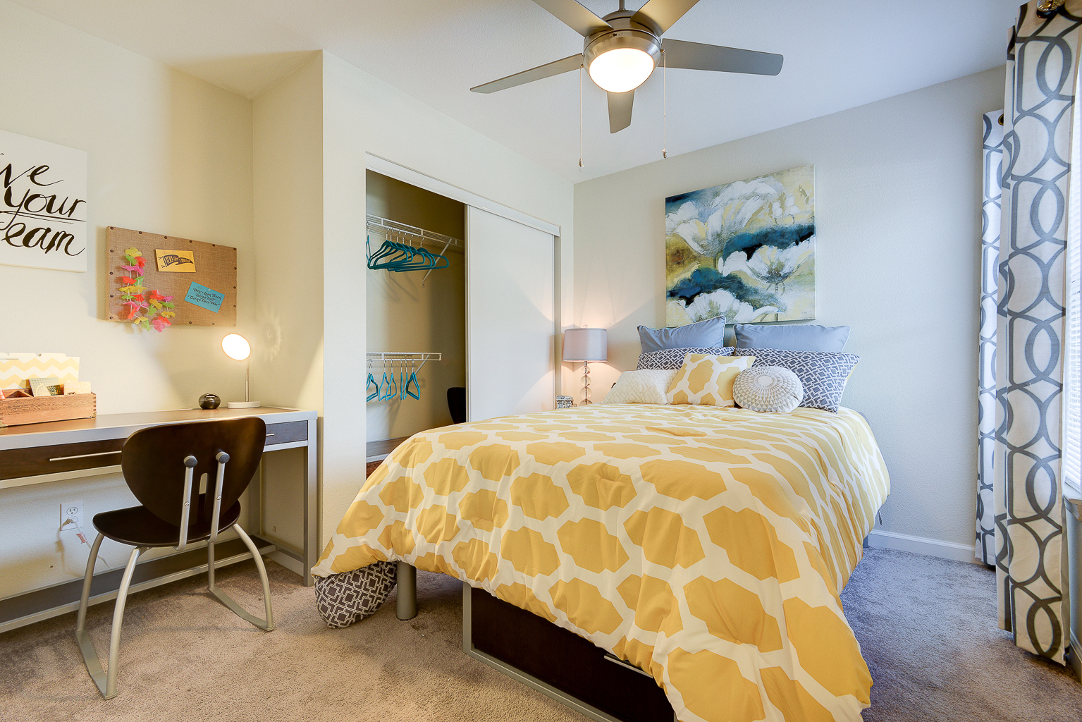 Interior of apartment bedroom with bed, closet, desk and ceiling fan