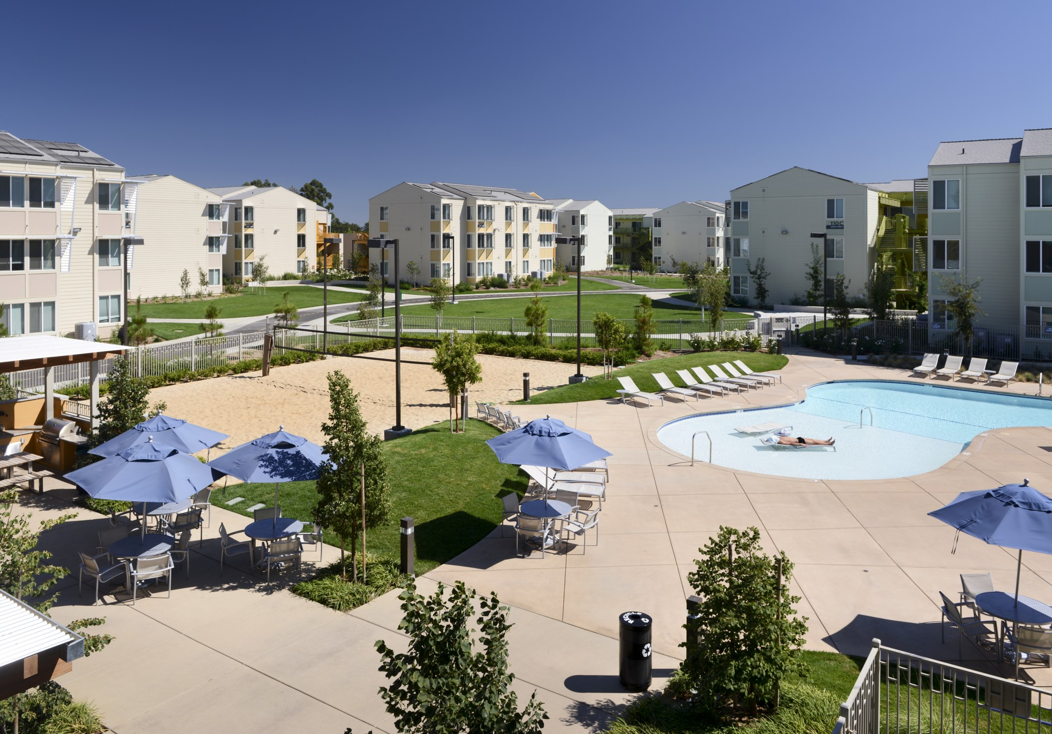 View of the pool, sand volleyball court, lounge chairs, and tables with umbrellas with apartment buildings in the background.