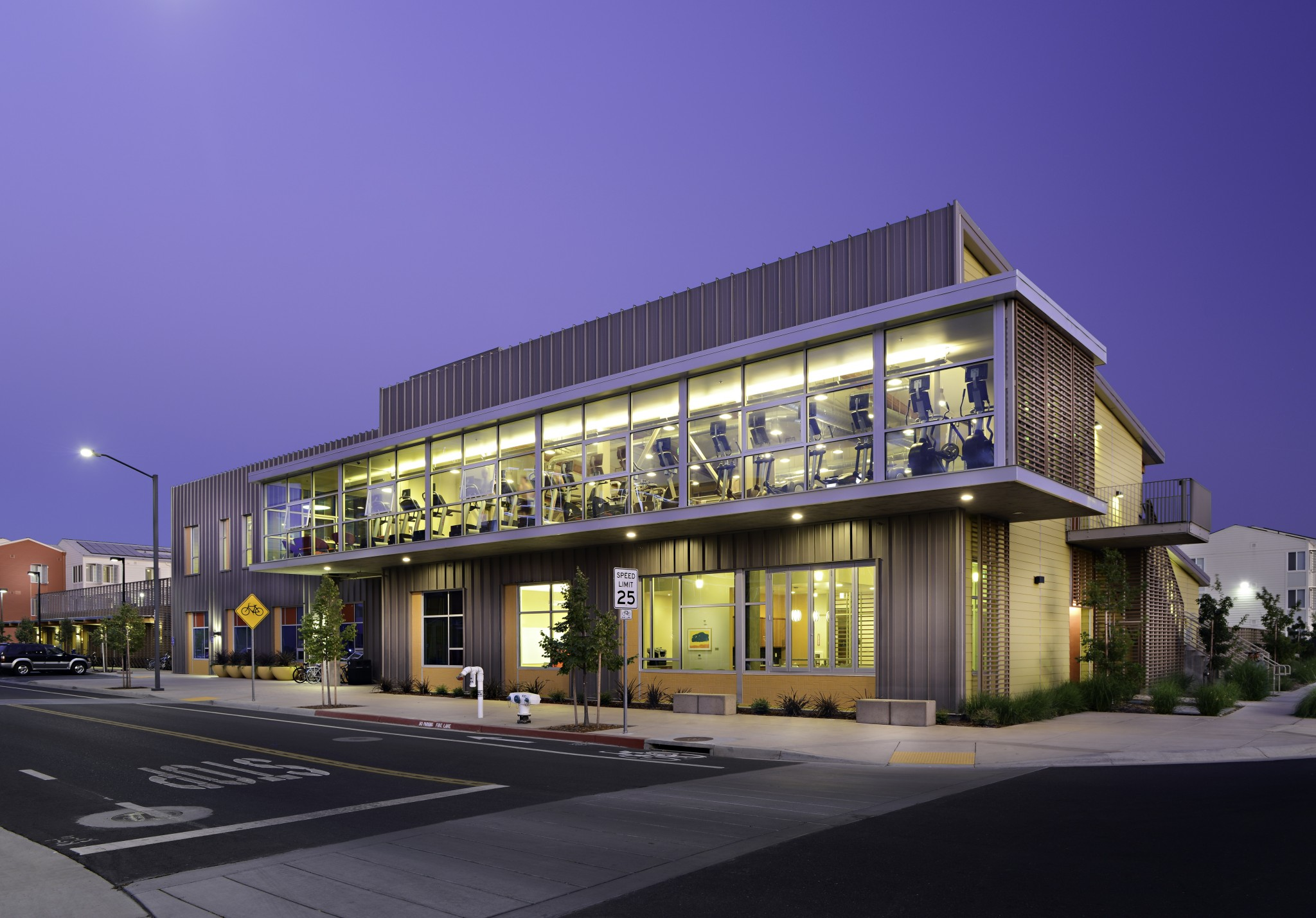 Exterior of modern building with a view of the fitness center on the second floor.
