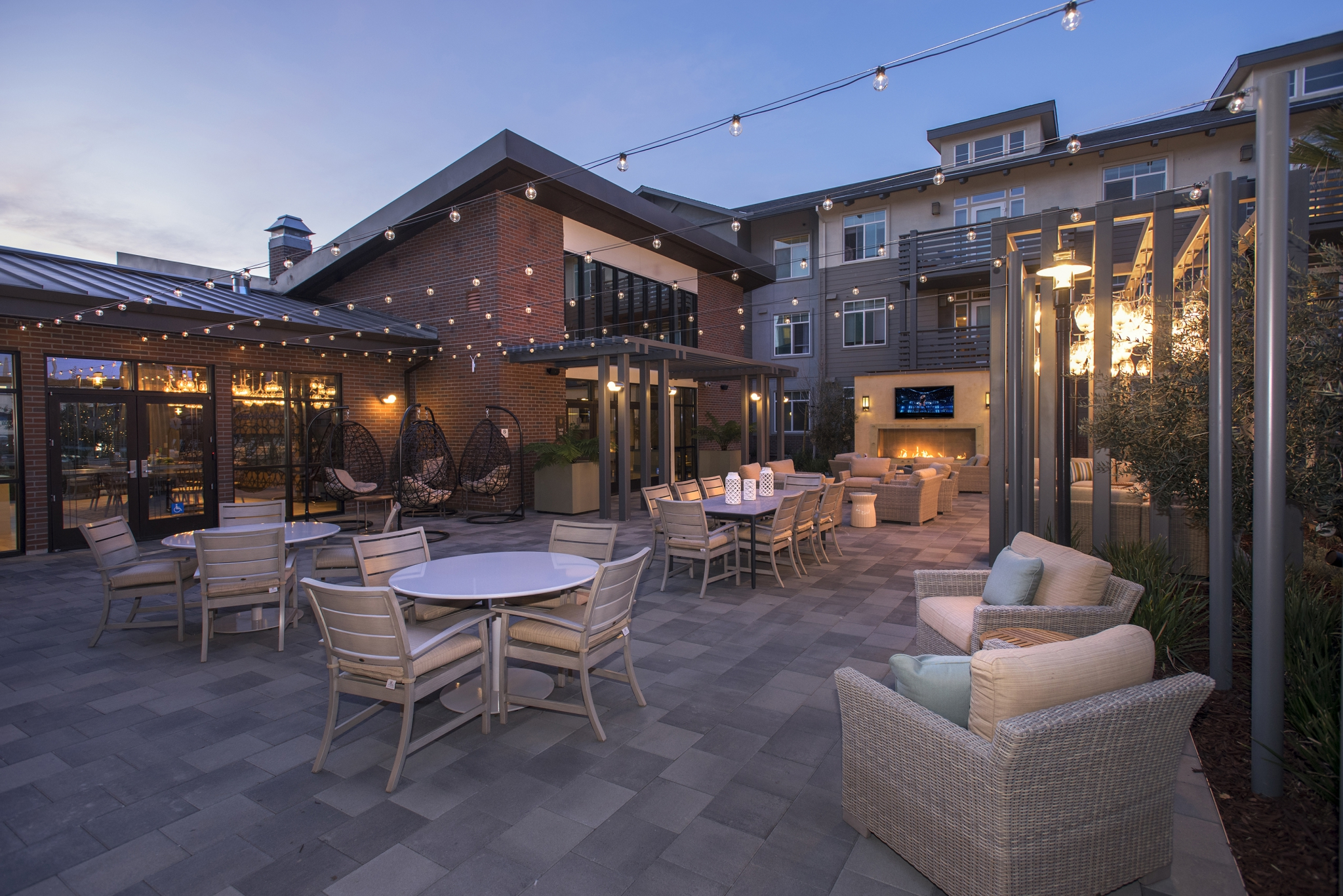 Exterior common area with dining tables, seating, fireplace and large-screen television surrounded by apartment buildings