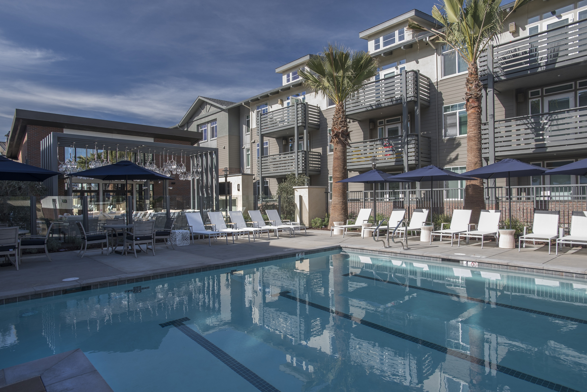 Exterior of pool with lounge chairs and umbrellas with 3-story apartment building with balconies in the background