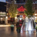 Exterior of restaurant with lit fountain in foreground