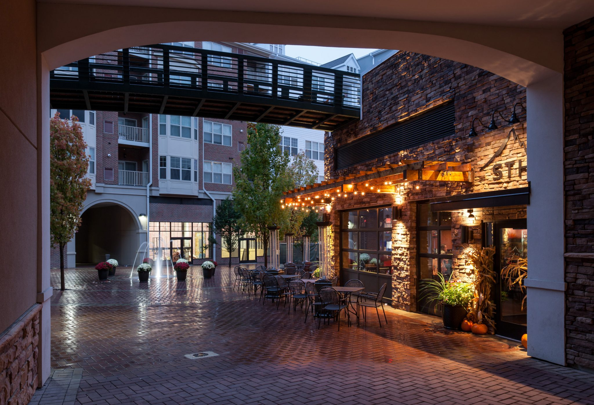 Exterior of courtyard with restaurant, fountain, and overhead walkway with apartment building in background
