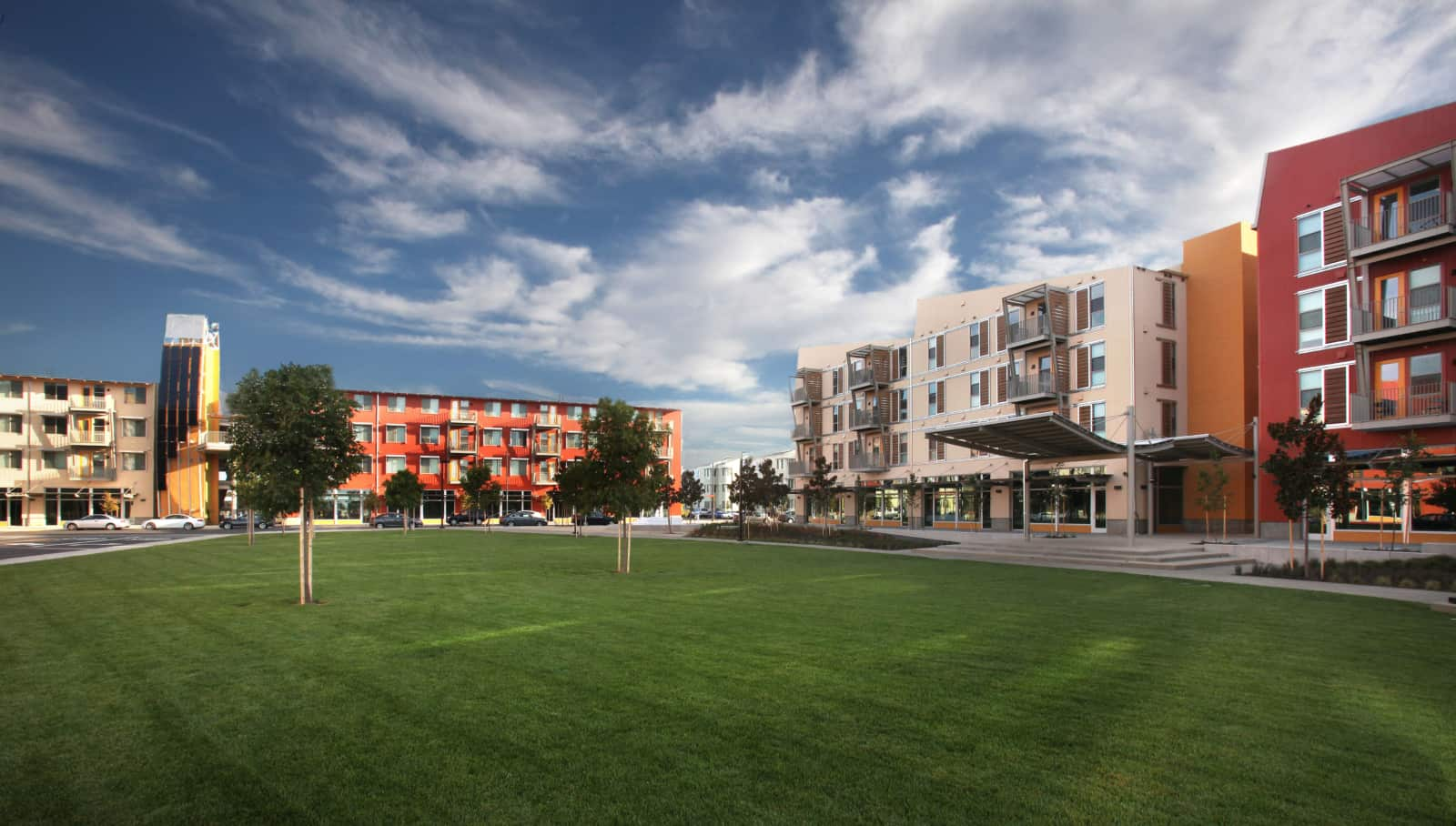 Exterior of several 4 story apartment buildings with a lawn in the foreground.