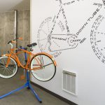 Interior with beach cruiser bicycle on work stand with bike graphic on wall behind it.